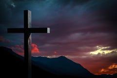 Croix de Jesus Christ au coucher du soleil Photos stock
