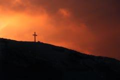 Croix de millénium lavée dans le coucher du soleil Photographie stock