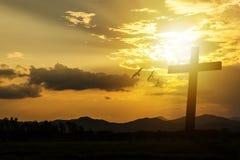 Croix de silhouette sur le fond de coucher du soleil de montagne Images libres de droits