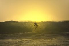 Croix de surfer de coucher du soleil une onde Photos stock