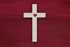 Croix en bois avec le coeur rouge sur le fond en bois rouge antique Photo stock