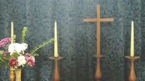 Croix en bois d'église entre les bougies et les fleurs clips vidéos