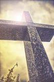Croix en pierre contre le ciel nuageux dramatique, effet de vintage Images libres de droits