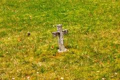 Croix en pierre sur la mousse et l'herbe Photos libres de droits