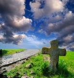 Croix en pierre sur la tombe négligée image stock