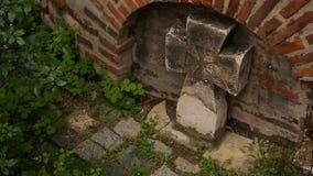 Croix en pierre tenant l'église proche, le symbole de la foi inconditionnelle et le culte banque de vidéos