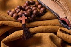 Croix et chapelet chrétien en bois et vieille bible sur un fond de draperie d'or de tissu photo stock