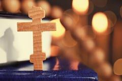 Croix et livres en bois contre des lumières Image libre de droits