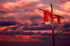 Croix et tunique sur un coucher du soleil Photo stock