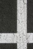 Croix formée perpendiculaire blanche sur l'asphalte noir Image libre de droits