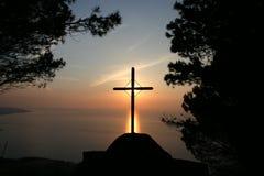 Croix latine sur le coucher du soleil Photographie stock