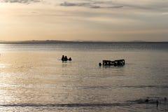 Croix-lumière des personnes dans le lac au coucher du soleil photos libres de droits