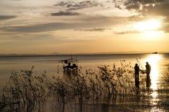 Croix-lumière des personnes pêchant dans le lac photo stock