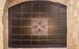 Croix maltaise sur une vieille, antique fenêtre dans le fort St Elmo, La Valette, Malte Vue par des murs images stock
