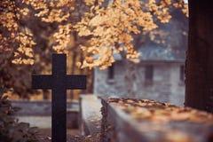 Croix noire dans le cimetière avec le mausolée photos stock