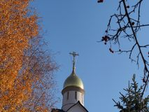 Croix orthodoxe encadrée par les feuilles d'automne jaunes des arbres images libres de droits