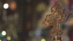 Croix religieuse d'or sur le fond des lumières dans l'église banque de vidéos