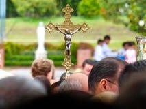Croix sainte d'or au-dessus des têtes des personnes avec le fond brouillé images stock