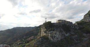 Croix sur la roche au-dessus du ciel nuageux clips vidéos