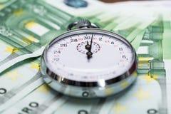 Cronómetro en billetes de banco Fotografía de archivo libre de regalías