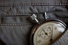 Cronômetro das antiguidades do vintage, no bolso cinzento da sarja de Nimes, medida do tempo do valor, minuto velho da seta do pu Foto de Stock