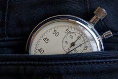 Cronômetro das antiguidades do vintage, no bolso traseiro novo da sarja de Nimes, medida do tempo do valor, minuto velho da seta  Fotografia de Stock Royalty Free