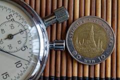 Cronômetro e moeda com uma denominação do baht 10 tailandês no fundo de madeira da tabela Foto de Stock