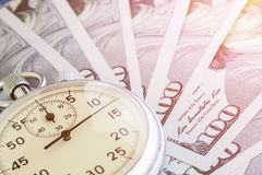 Cronômetro um fundo do close up do dinheiro, tonificado imagem de stock royalty free