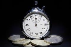 Cronômetro velho em um fundo preto com dinheiro Foto de Stock