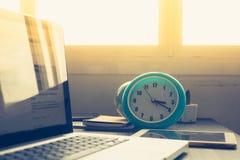 Cronometre com o portátil na mesa e na luz do sol de escritório na tarde Imagens de Stock Royalty Free