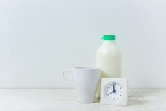Cronometre no tempo de manhã, leite no fundo de madeira Foto de Stock