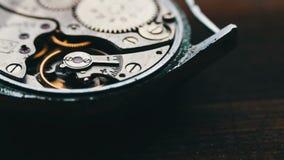 Cronometre o mecanismo de engrenagens, em um fundo de madeira à moda video estoque