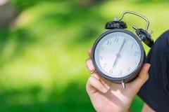 Cronometri a disposizione il tempo di manifestazione all'orologio del ` di 6 o sul parco verde Immagine Stock Libera da Diritti