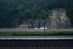 Cronometri e prepari la pista vicino al villaggio tedesco Schona in priorità alta ed alle case con grande roccia in villaggio cec Fotografie Stock