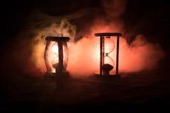 Cronometri il concetto La siluetta dell'orologio della clessidra ed il fumo su fondo scuro con il freddo blu rosso giallo arancio Immagini Stock Libere da Diritti