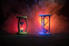 Cronometri il concetto La siluetta dell'orologio della clessidra ed il fumo su fondo scuro con il freddo blu rosso giallo arancio Fotografia Stock