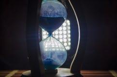 Cronometri il concetto La siluetta dell'orologio della clessidra ed il fumo su fondo scuro con il freddo blu rosso giallo arancio Fotografie Stock Libere da Diritti