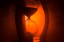 Cronometri il concetto La siluetta dell'orologio della clessidra ed il fumo su fondo scuro con il freddo blu rosso giallo arancio Immagine Stock Libera da Diritti