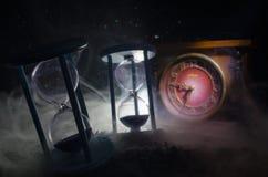 Cronometri il concetto Siluetta dell'orologio e del fumo della clessidra su fondo scuro con illuminazione giallo arancione calda, Fotografia Stock Libera da Diritti