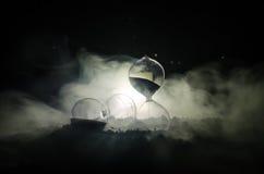 Cronometri il concetto Siluetta dell'orologio e del fumo della clessidra su fondo scuro con illuminazione giallo arancione calda, Fotografia Stock