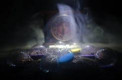 Cronometri il concetto Siluetta dell'orologio e del fumo della clessidra su fondo scuro con illuminazione giallo arancione calda, Fotografie Stock