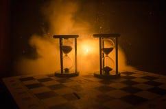Cronometri il concetto Siluetta dell'orologio e del fumo della clessidra su fondo scuro con illuminazione giallo arancione calda, Immagine Stock