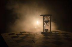 Cronometri il concetto Siluetta dell'orologio e del fumo della clessidra su fondo scuro con illuminazione giallo arancione calda, Immagine Stock Libera da Diritti