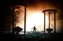 Cronometri il concetto Siluetta di un uomo che sta fra le clessidre con fumo e le luci su un fondo scuro Immagine Stock