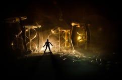 Cronometri il concetto Siluetta di un uomo che sta fra le clessidre con fumo e le luci su un fondo scuro Fotografie Stock Libere da Diritti