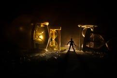 Cronometri il concetto Siluetta di un uomo che sta fra le clessidre con fumo e le luci su un fondo scuro Fotografia Stock