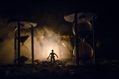 Cronometri il concetto Siluetta di un uomo che sta fra le clessidre con fumo e le luci su un fondo scuro Fotografia Stock Libera da Diritti