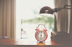 Cronometri su legno di mattina, fondo vago della camera da letto immagini stock