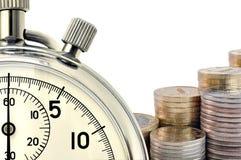 Cronometro e monete Immagine Stock