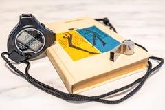 Cronometro nero, libro di formazione e fischio su un piatto di marmo immagine stock libera da diritti